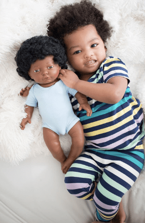 Young child holding onto a doll that looks like him. Find dolls that reflect your reality.