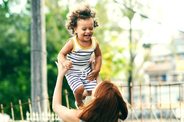 Red haired mother lifting a curly haired mixed child. Start supporting your kids against racism at an early age.