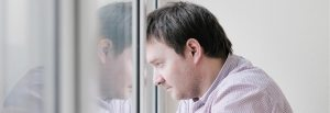 A photograph of a man with his head pressed against a window looking sad.