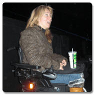 Clare sits in her powerchair in the front row of the cinema, it is dark and she has a soft drink resting on the tray of her Trabasack