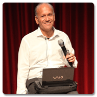 Doug sits on a stool, holding a microphone, he smiles towards the camera with a red pleated curtain behind him and a laptop atop the Trabasack on his lap