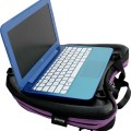 Image is a photograph of the Trabasack Curve with purple trim with a blue laptop on the tray surface