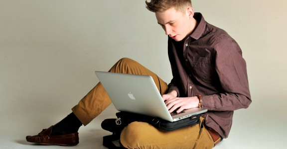 Young man sitting upon the floor using the Trabasack Mini upon his lap for his laptop