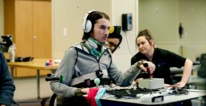 a disabled gamer sits at a table with a serieof adapted controls for gaming within his reach
