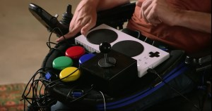 Close up view of a Trabasack Curve Connect upon Zach Anner's lap, with a XAC, Buddy Buttons and Joystick