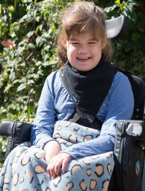 Image shows a photograph of a smiling young girl with brown hair, sat outside in a wheelchair, wearing a black towelling kerchief around her neck with a blue and beige leopard print fleece blanket covering her knees