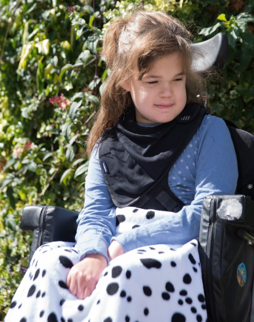 Image shows a photograph of a young girl in a wheelchair, sat outside, looking off camera to the right, wearing a black jersey kerchief