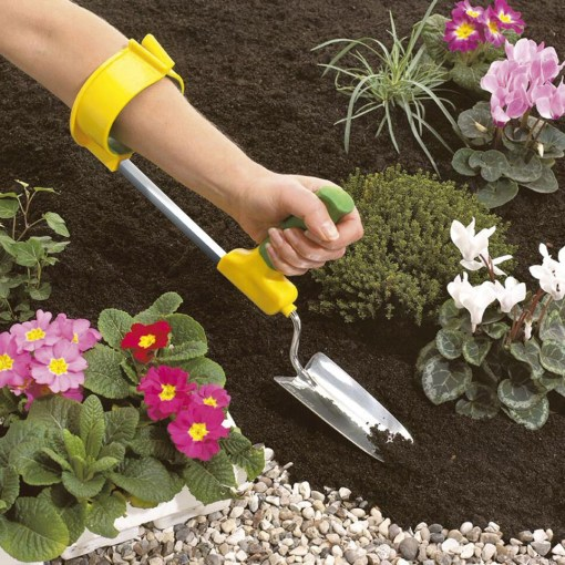 Image is a photograph of an outstretched arm, in a garden, wearing an easi-grip arm support cuff with a trowel attached to the end