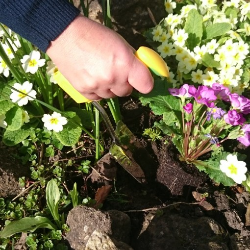 Image is a photograph of a man holding an easi-grip trowel in his hand, whilst turning soil in a flower bed outdoors