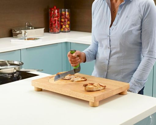 Image is a photo of a woman in a blue shirt slicing chicken breasts on a wooden cutting board in a blue and white kitchen