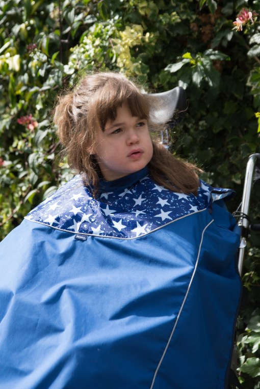 Image shows a photograph of a brown-haired girl sat outside in a wheelchair wearing a Royal Blue and White Star design waterproof total wheelchair cover