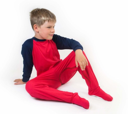 Image shows a photograph of a boy with light brown hair, sat casually on the floor wearing a Seenin jersey sleepsuit in navy blue and red
