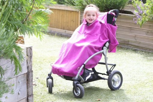 Image is a photograph of a girl smiling at the camera, whilst sat in an SEN stroller whilst covered with a fuchsia pink total fleece cover