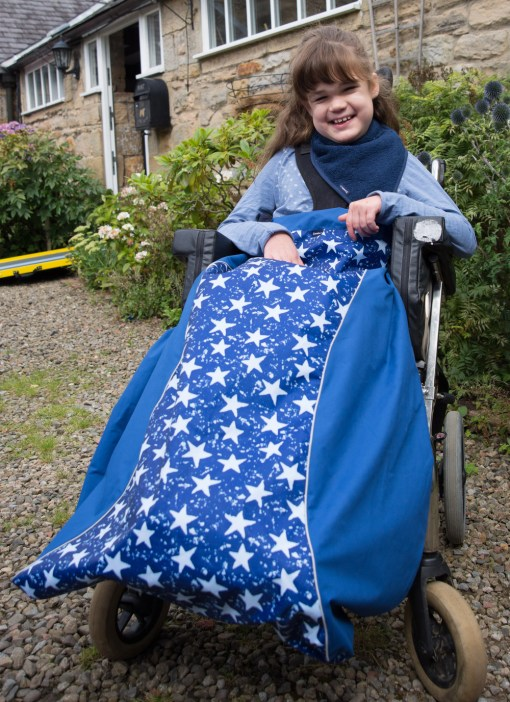 Image is a photograph of a brown-haired girl with a broad smile, sat outside a stone house in a wheelchair wearing a royal blue and white star print wheelchair leg cover