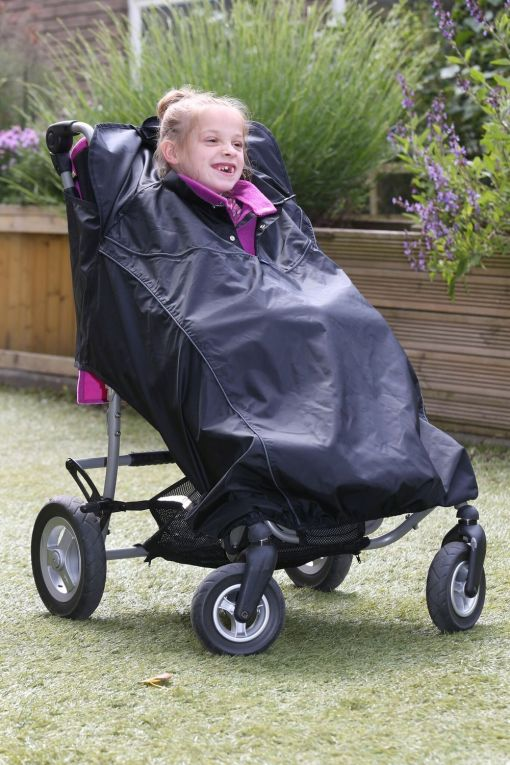 Image is a photograph of a smiling girl outdoors, sat in an adaptive SEN stroller, wearing a Seenin total wheelchair protector