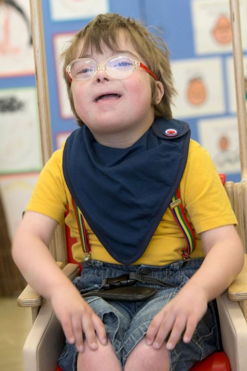 Image shows a photograph of a cheerful young boy wearing brightly coloured trouser braces and t-shirt, and a navy blue kerchief around his neck