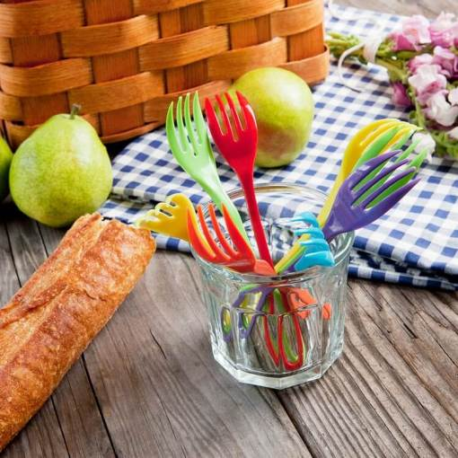 Image is a photograph of an outdoor, wooden table with a picnic basket and checked cloth, surrounded by fruit and bread, with a small glass containing several colourful Knorks