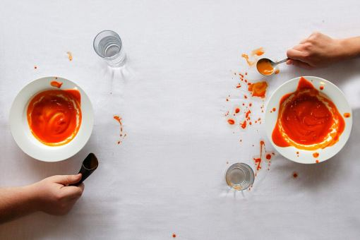 Image is a photograph of two bowls of tomato soup at either end of a clothed table. Next to the first bowl sits a S'Up Spoon with relatively little mess to the table cloth. Next to the second bowl sits a traditional soup spoon, with tomato soup spillage on the table cloth