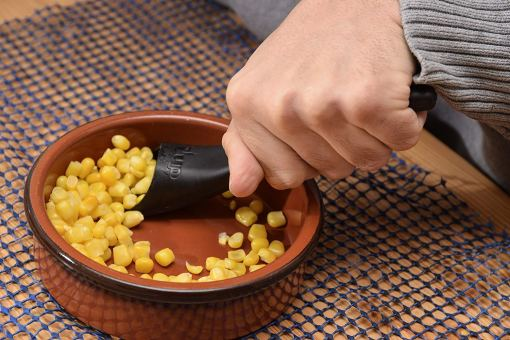 Image is a photograph of the S'Up Spoon being used to scoop-up sweetcorn