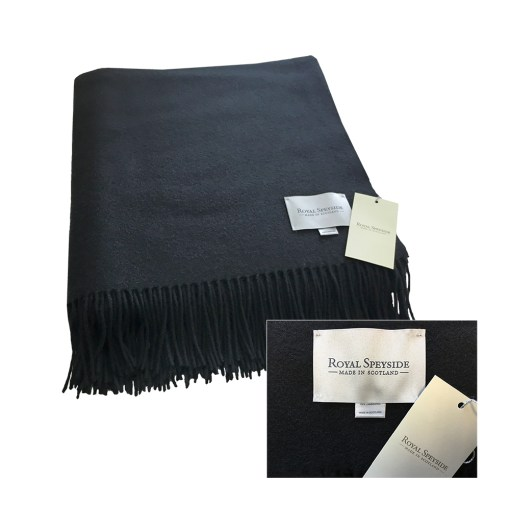 Image is a photograph of a black woollen blanket with created by Royal Speyside - Made in Scotland