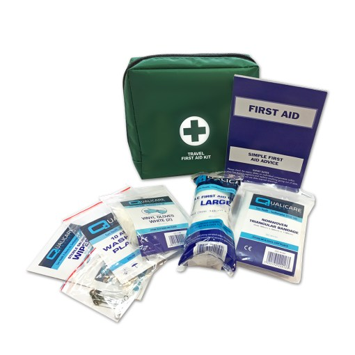 Image is a photograph of a green first aid kit bag, with various first aid contents around it