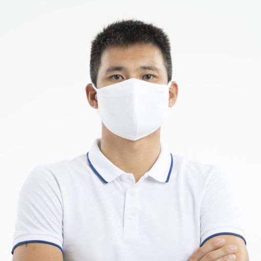 Image is a photograph of a man in a white polo shirt, arms crossed, wearing a white fabric face mask