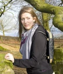 A lady climbs a rock whilst wearing a Trabasack Mini lap tray bag with yellow trim