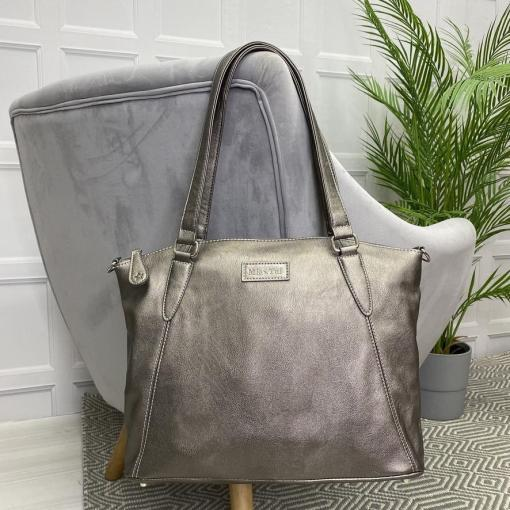 Image is a photograph of a Metallic Grey Samantha Renke accessible handbag in the extra size, hanging by the straps over the back of a grey velvet chair in a living room.