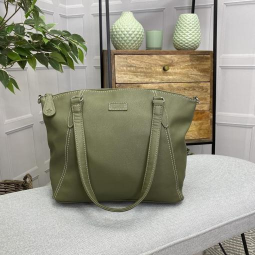 Image is a photograph of the Samantha Renke accessible handbag in Olive on a white table in a modern living room