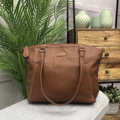 Image is a photograph of the Samantha Renke accessible handbag in Tan on a white table in a modern living room