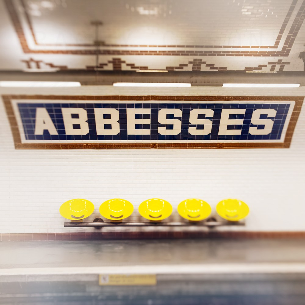Colorful yellow seats in the Abbesses Metro stop in Paris France by Tracey Capone