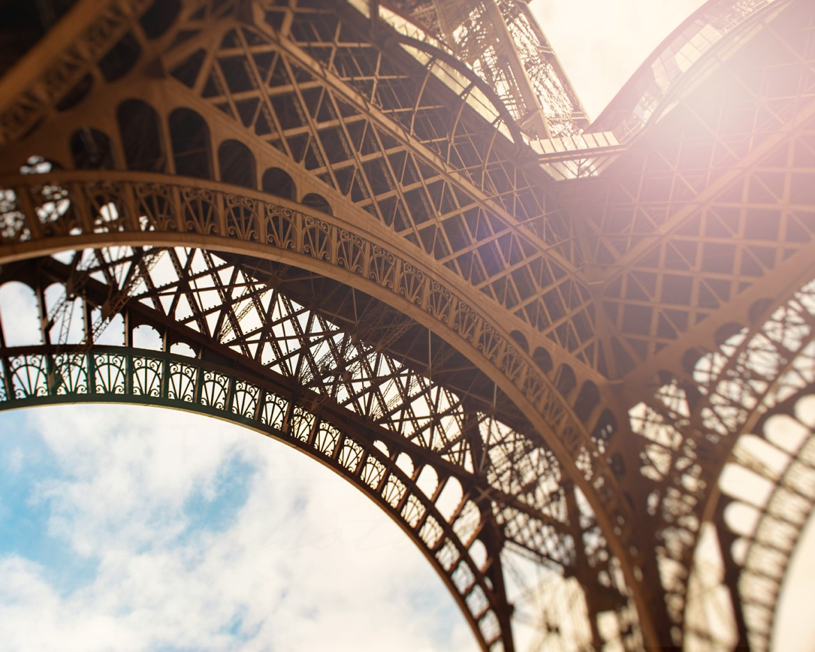 Abstract photograph of the Eiffel Tower in Paris, as seen from beneath with the sun shining through. Photograph by Tracey Capone