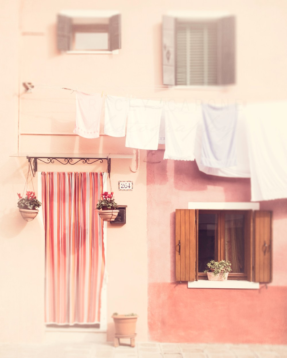 A light pink home with laundry hanging on the island of Burano, Italy. Landscape and travel photography by Tracey Capone.