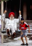 A Sikh child pushes his grandfather on a swing in a park in the northern Indian city Chandigarh August 13, 2006. REUTERS/Kamal Kishore (INDIA)
