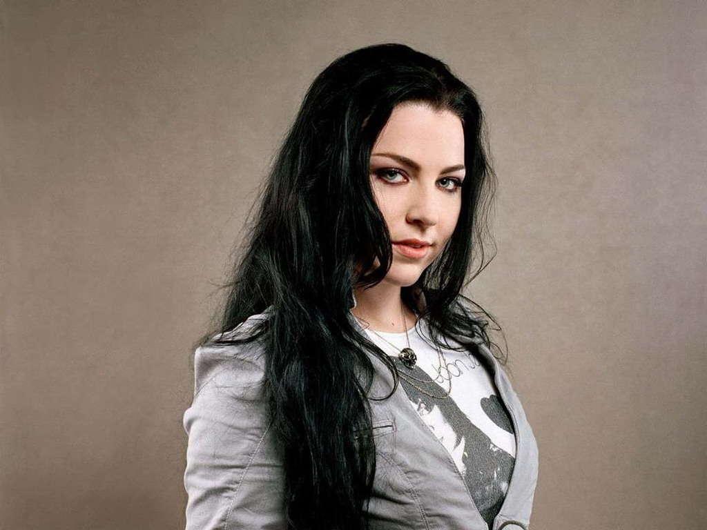 Ammy Lee posa de perfil usando uma camisa branca estampada, com um casaco cinza e atrás uma parede marrom.