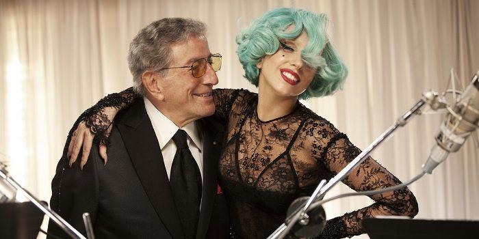 tony bennett e lady gaga a frente de microfones. Tony de terno e óculos  abraçando Gaga que usa um vestido de renda e um cabelo verde