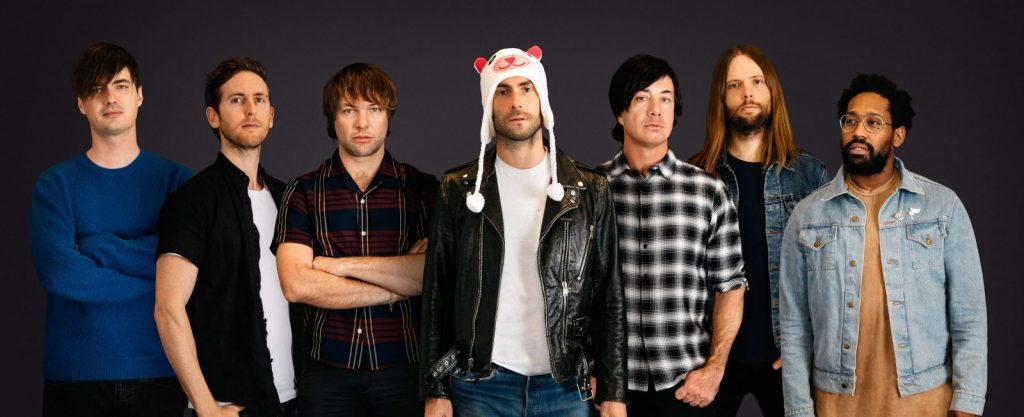 maroon 5 e megan stalion A banda maroon 5 em uma foto. Os 7 membros da banda, Adam Levine, vocalista no meio com gorro de unicórnio na cabeça