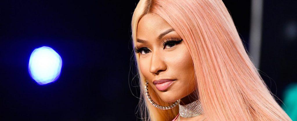 Nicki Minaj e Selena Gomez já pensaram em parar de fazer música. Na foto, a rapper está de cabelo rosa, usando brinco e um colar de diamante.