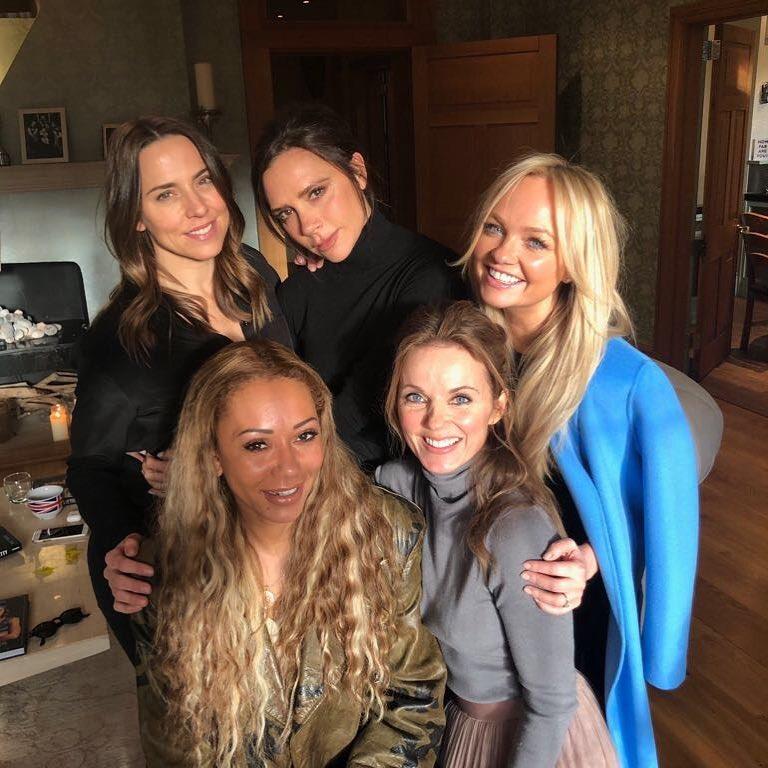 Girlgroup Spice Girls reunido com as cinco integrantes em sala, duas estão sentadas e as três restantes em pé.