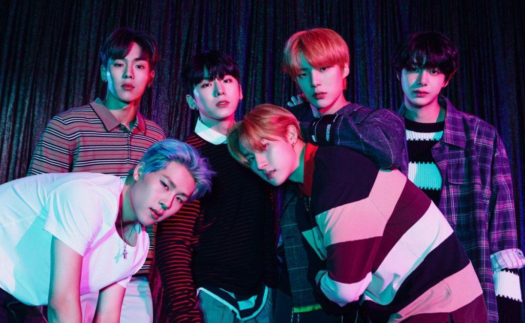 grupo de k-pop retirado do spotify Monsta X com 6 integrantes, todos em pé, com cabelos coloridos, usando casaco e camisas de manga comprida. O do lado direito o único com camisa branca sem manga comprida