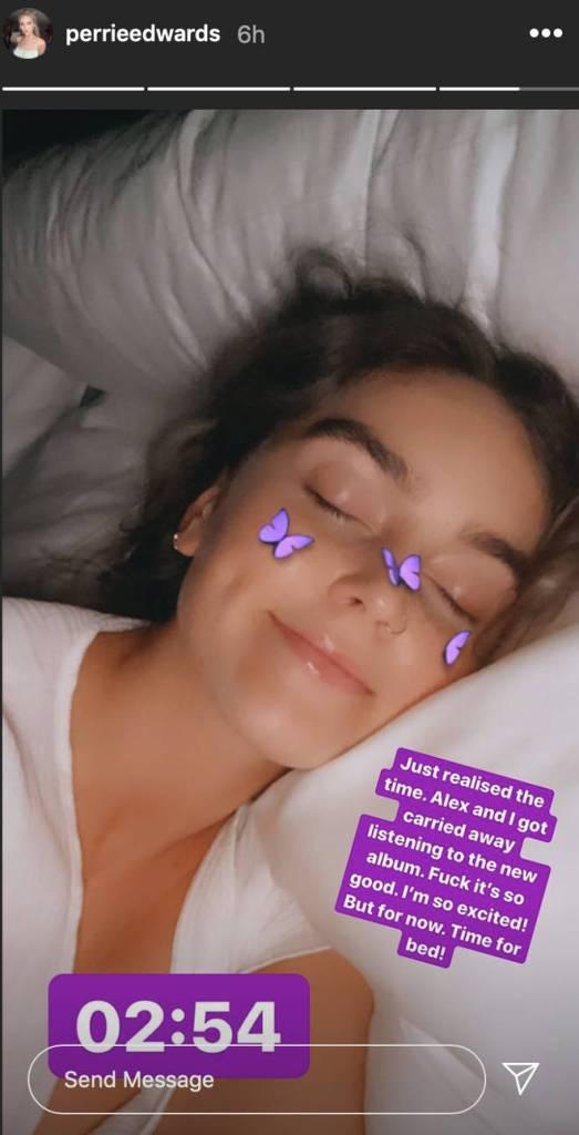 Story do Instagram de Perrie Edwards, integrante do Little Mix, contando sobre ter ouvido algumas músicas do disco novo. Perrie está na cama, de olhos fechados e sorrindo.