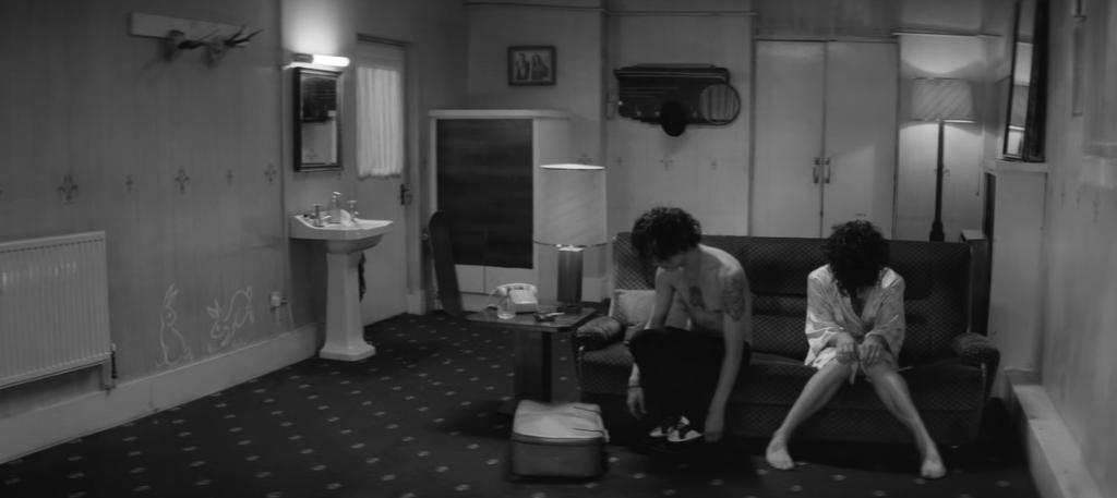 """Matty Healy, vocalista do The 1975, no clipe de """"Somebody Else"""". Matty aparece num cenário preto e branco, e com um clone de si mesmo. Os dois estão sentados num sofá, encarando o chão."""