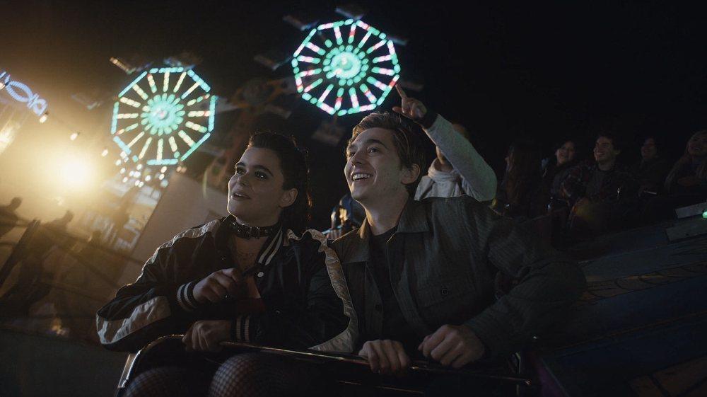 Na foto, os personagens de Euphoria Kat e Ethan estão em um brinquedo giratório de um parque de diversões. Ao fundo, é possível ver algumas pessoas e outros brinquedos iluminados, em formato redondo. Nesse episódio é tocada Euphoria Funfair, música da trilha sonora de Euphoria.