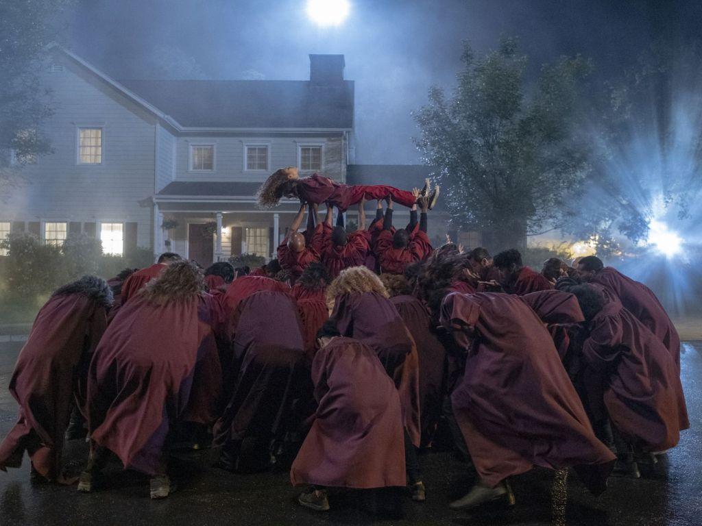 Na foto, cena de Euphoria em que Rue, personagem principal, é erguida, deitada, no meio da rua, por diversos figurantes que vestem vestes vermelhas, assim como ela, em uma performance musical que acontece no fim da série. Nesse momento, a personagem canta All For Us, da trilha sonora de Euphoria.