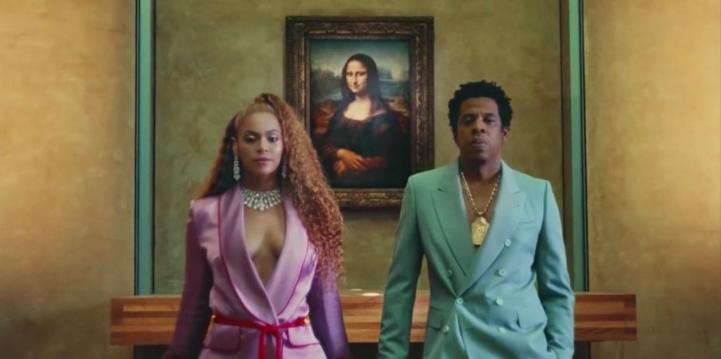 Beyoncé e Jay Z no clipe de apeshit na frente da pintura de Monalisa que  fica no Louvre. Jay usa terno verde e um cordão de ouro grande e Bey uma roupa rousa com brincos e colar de diamante. Na matéria de Bruno Mars e Anderson Paak