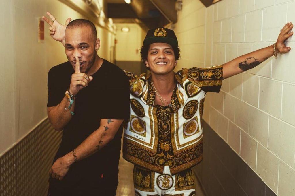Bruno Mars e Anderson Paak juntos em um corredor. Bruno usando um boné preto e uma camisa de manga marrom e branca estampada. Anderson Paak de blusa preta e com o dedo na boca fazendo final de silêncio.