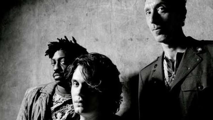 O John Mayer trio em uma foto preto e branco. Todos olhando para a câmera