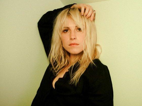 hayley loira com a mão na cabeça, encostada em uma parede da cor bege e usando uma camiseta preta