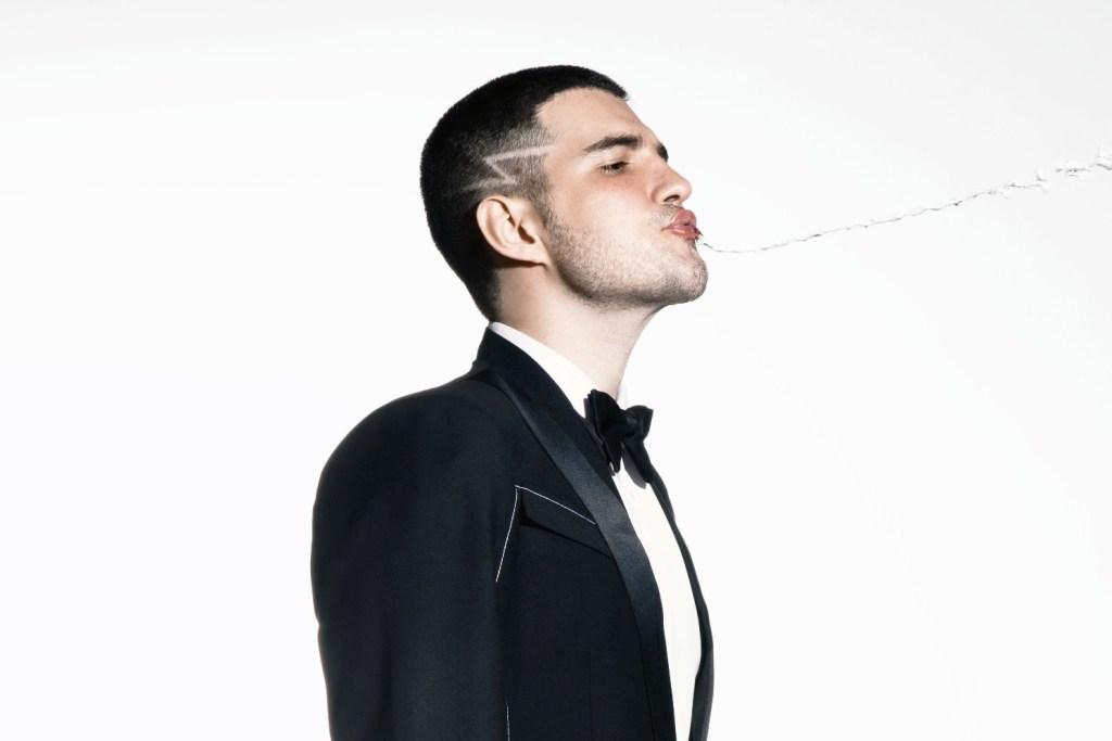 """Em uma imagem promocional de seu novo single """"Coringa"""", Jão aparece vestido com um terno e uma gravata borboleta, virado para a direita e com a cabeça erguida enquanto cospe água para o mesmo lado."""
