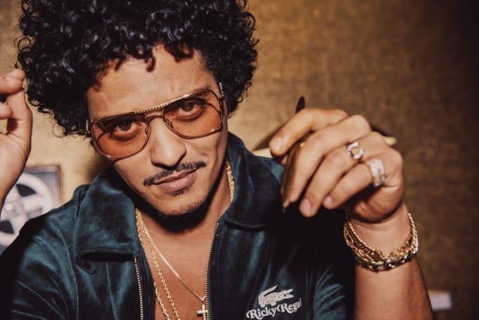 Bruno Mars posa para sua marca de roupas da lacoste. Ele usa um óculos de aviador marrom, anéis de ouro, uma pulseira e cordões de ouro com uma crua. Na mão ele segura uma caneta e usa de moletom de veludo verde